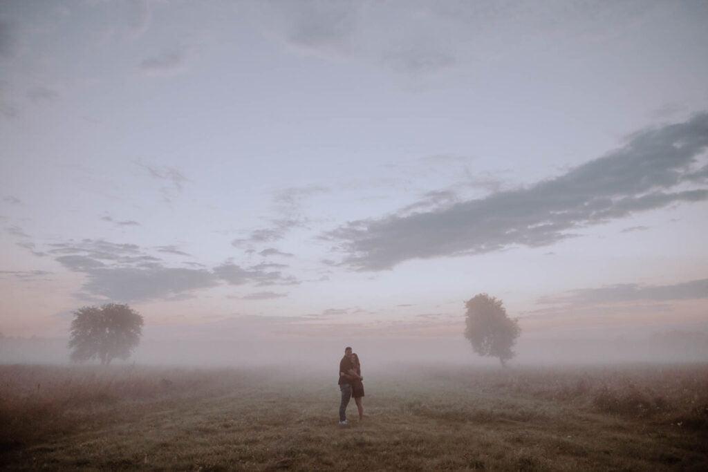 Poranna mgła, drzewa i dwójka zakochanych