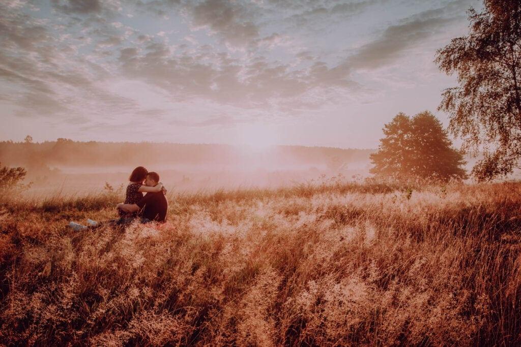 Ania i Oskar przytulają się pośród złotej trawy