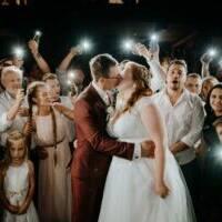 Goście weselni oświetlają młodą parę latarkami
