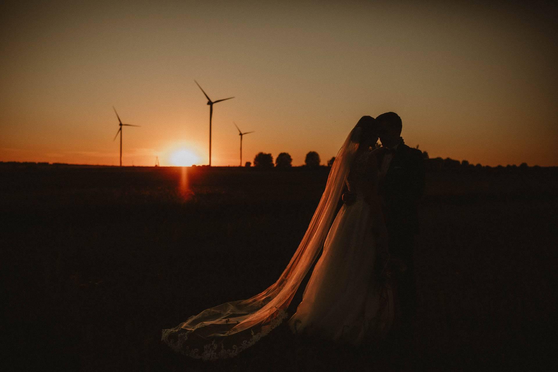 Sesja plenerowa o zachodzie słońca, w tle turbiny wiatrowe
